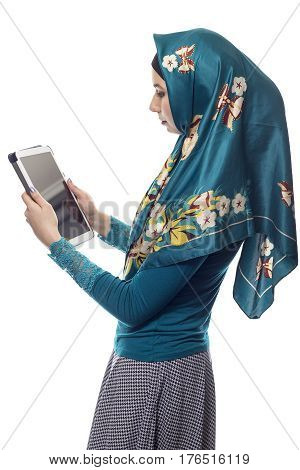 Female wearing a green hijab reading news online on a tablet or social networking via mobile device. She is isolated on a white background. The conservative outfit is associated with muslims and middle eastern culture.