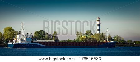 Blue cargo ship leaving Riga and entering Baltic sea