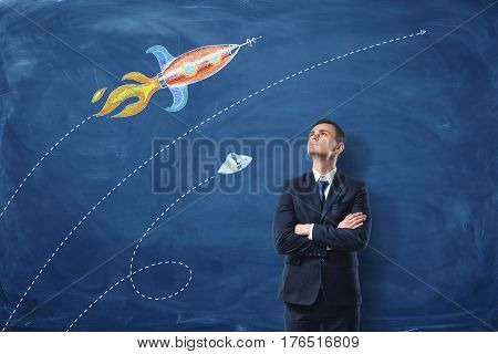 A businessman standing with his arms folded on the dark blue background, he is looking up at the pictures of the rocket and the UFO drawn on the wall. Long-range plans. Flights of imagination. Looking for inspiration.