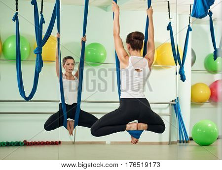 Young attractive woman practicing anti-gravity yoga with a hammock