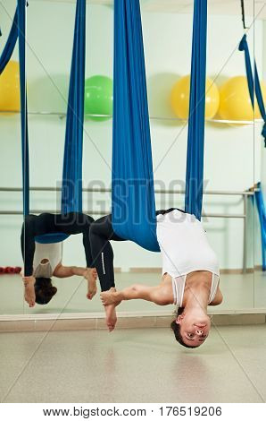 Upside down woman doing aerial yoga with assistance of hammock