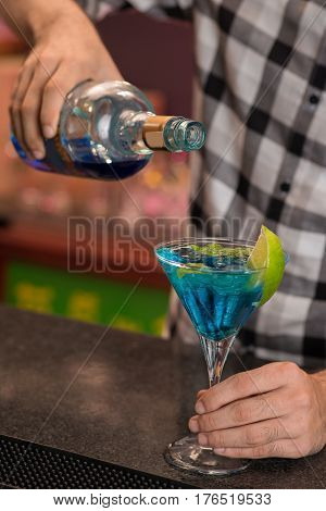 Hands of barman pouring blue liqueur in the glass