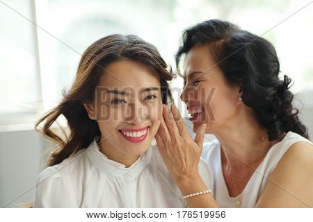 Mature Asian woman telling secret to her daughter