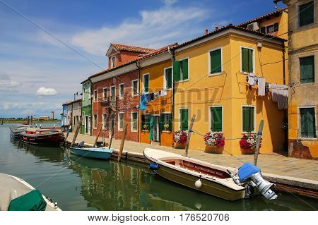 Colorful houses by canal in Burano Venice Italy. Burano is an island in the Venetian Lagoon and is known for its lace work and brightly colored homes.