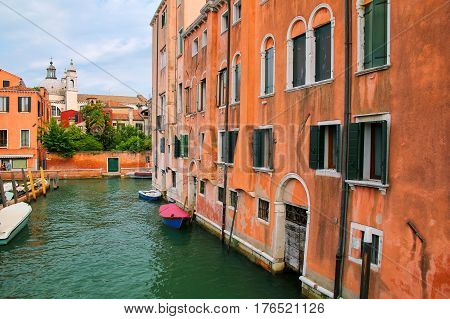 Narrow Canal Lined With Houses In Venice, Italy