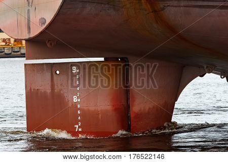 Red big cargo ship's stern close up