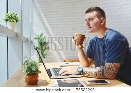 Pensive young man drinking coffee to get some energy boost