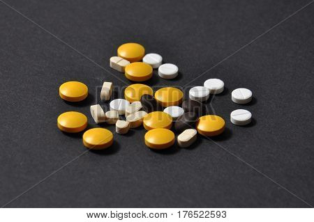 Tablets and pills on dark background. Lot of different pills on black background