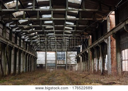 Abandoned industrial interior. Prefabricated concrete frame plant shop.