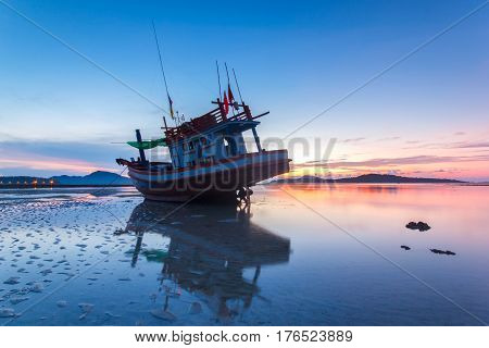 Fishing boat with the sunrise in the sea with reflection and cloud at the Rawai beach Phuket Province Thailand