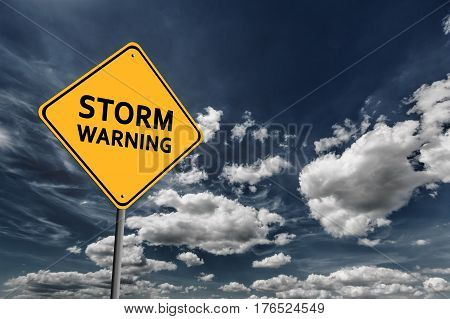 Background of dark blue sky with cumulus clouds and yellow road sign with text Storm Warning