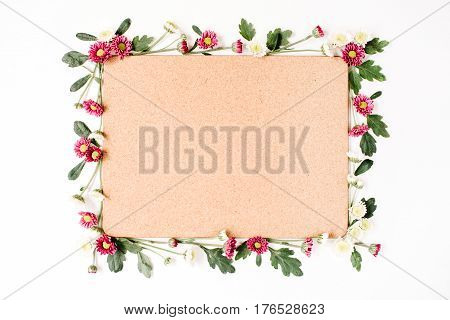 Frame with red and white wildflowers green leaves branches and wooden cork tree board on white background. Flat lay top view. Flower background.