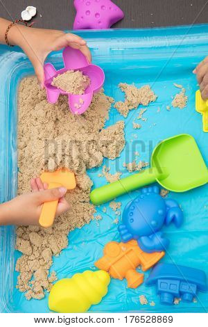 Child's Hand Close Up Playing Kinetic Sand