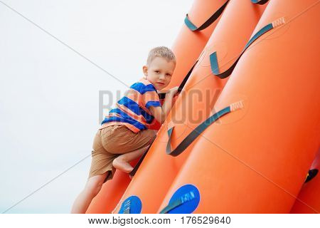 Little Boy Playing On An Inflatable Playground On The Beach