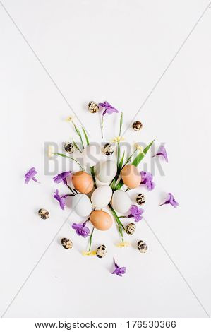 Brown and white Easter eggs quail eggs yellow and purple flowers on white background. Flat lay top view. Traditional spring concept. Easter concept.