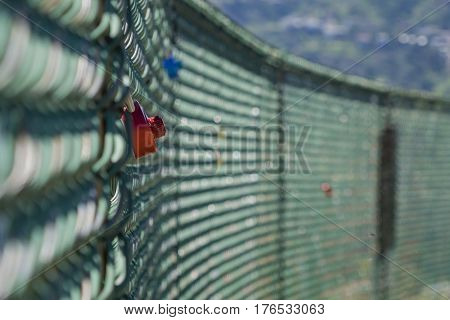 Red lock locking at a fence on morning