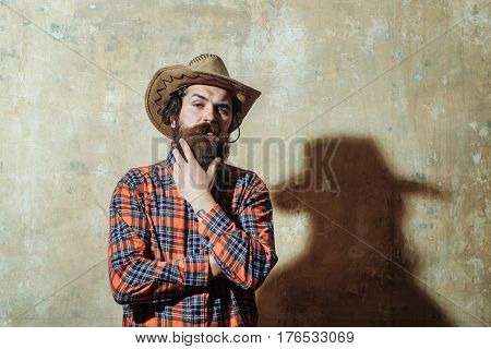 Bearded Man In Cowboy Hat And Black Shadow On Wall