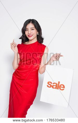 Beautiful asian woman wearing a red dress with shopping bag and holding credit card standing over white.