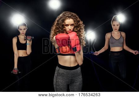 Attractive Sportswomen Boxing, Training With Dumbbells And Jumping On A Skipping Rope On Black