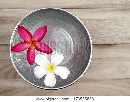 red and white flowers floating in silver bowl on wooden floor background, for Songkran festival in Thailand, top view