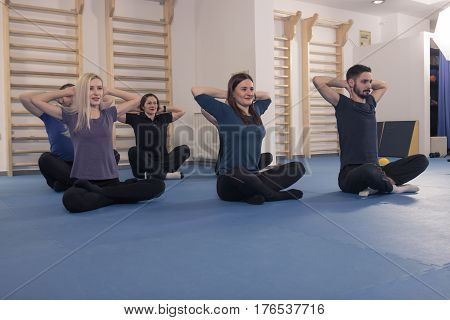 group six people warm up stretch lying laying floor