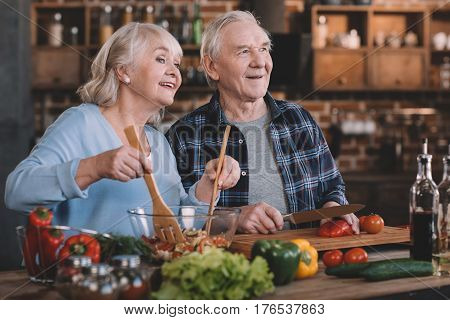 Portrait Of Senior Couple Looking Away While Cooking Together