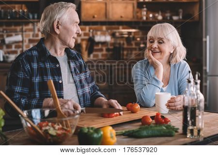 Happy Senior Couple Cooking Together At Kitchen Table