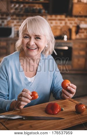 Happy Senior Woman Holding Tomatoes While Cooking At Kitchen