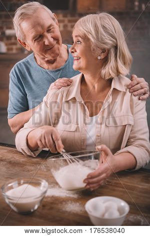 Senior Couple Cooking Pancakes On Kitchen At Home