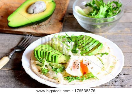 Vegetarian breakfast with a poached egg, avocado slices, cabbage, lettuce mix, tortilla, sauce and spices. Egg and avocado breakfast tortilla recipe. Fork, avocado half on a wooden table