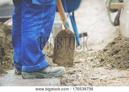 Construction worker wotking hard and leveling concrete pavement outdoors.