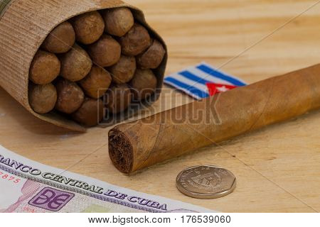 Luxury Cuban cigars and money on the wooden table