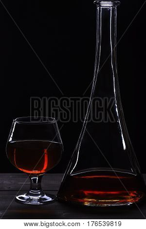 Glass And Carafe With Cognac On Black Wooden Table