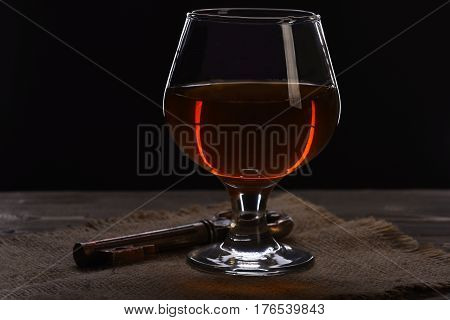 Glass With Cognac, Whiskey And Key On Wooden Table