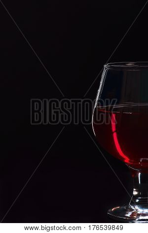 Glass With Cognac Or Whiskey Isolated On Black Background