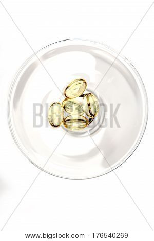 Capsules Of Cod-liver Oil In Glass Isolated On White Background