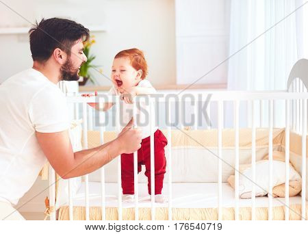 Happy Father Playing With Infant Baby In The Cot At Home