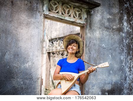 Happy woman sitting smiling and playing music with balalaika at grey wall background. Lifestyle concept. Jam session. Russian instrument.