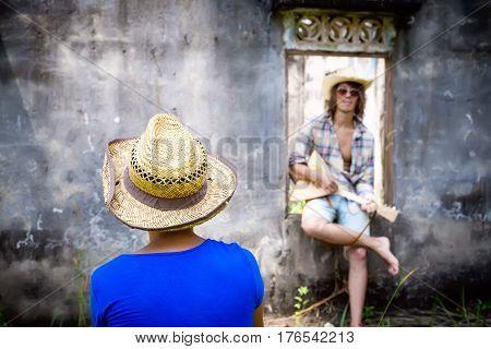 Woman Looking At Man Playing Music At Grey Wall Background