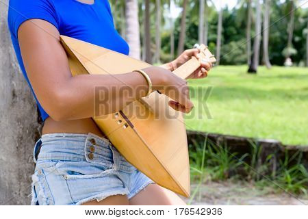 Woman playing music with balalaika at grey wall background.. Lifestyle concept. Jam session. Russian instrument.