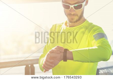 Urban jogger checking his running time outdoors.