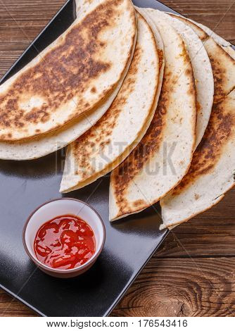 Tortilla with chicken, ketchup on black plate at wooden table