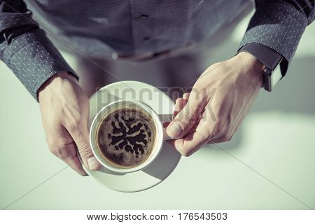 Close-up partial view of stylish man with smartwatch on hand holding coffee cup