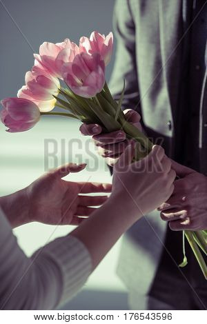 Close-up partial view of man presenting beautiful tulips to woman
