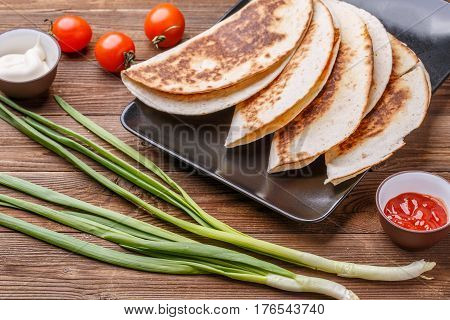 Photography of quesadillas with chicken on wooden table