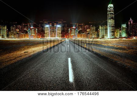 Empty road at night with a city lights in the background