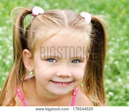 Adorable smiling little girl on the meadow in summer day
