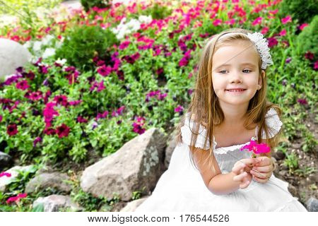 Adorable little girl in princess dress with flower sitting in the park outdoors