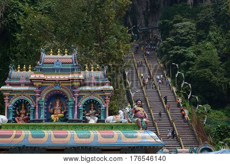 Kuala Lumpur Malaysia - November 3 2014: Statues of Hindu gods on the roof of the temple next to Stair leading to the top Batu Caves - complex of cave hills and Hindu shrines at a distance of 13 km from the center of Kuala Lumpur.