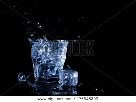 Water splash in a glass. A glass of cold water. Cold water with ice